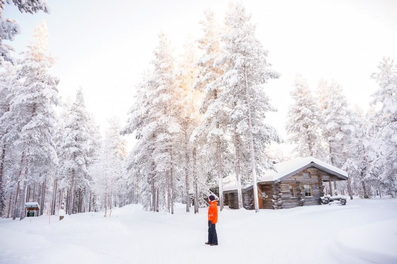 person in orange coat standing in front of log cabin and trees with snow on them