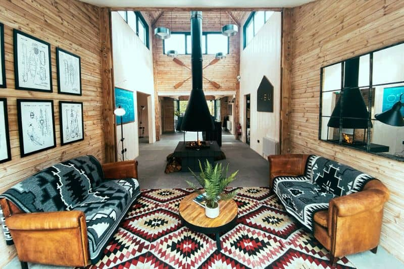 Cabu Hideaways Log cabin interior with patterned rugs and throws and a tall wood burner at the end of a long room