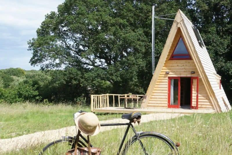 A-frame log cabin in a grassy field with a bike in front