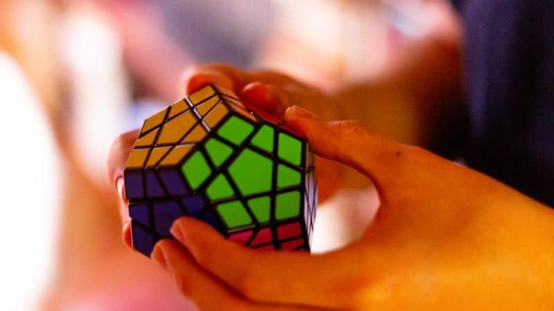 hands holding a pentagonal Rubik's cube