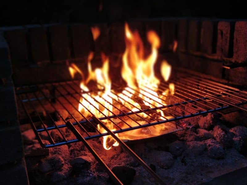 charcoal fire and flames under BBQ grill