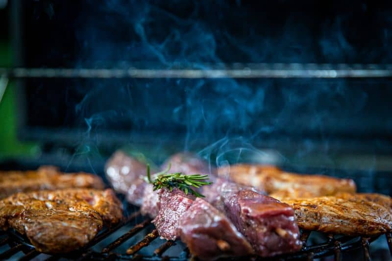 meat cooking on BBQ with rosemary sprig
