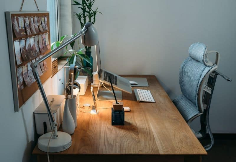 work from home desk with ergonomic chair tucked under wooden desk with a lamp, Apple mac on a stand and a keyboard and mouse