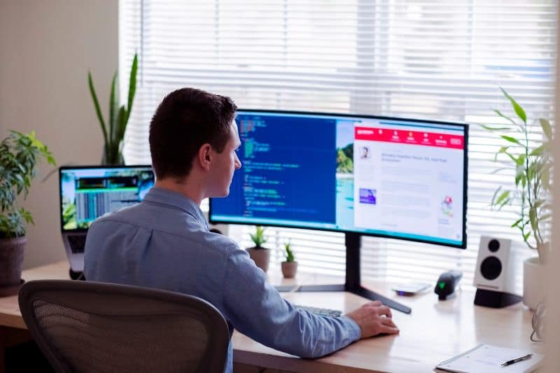 Man in shirt sat at office in front of curved monitor flanked by green potted plants, facing a window