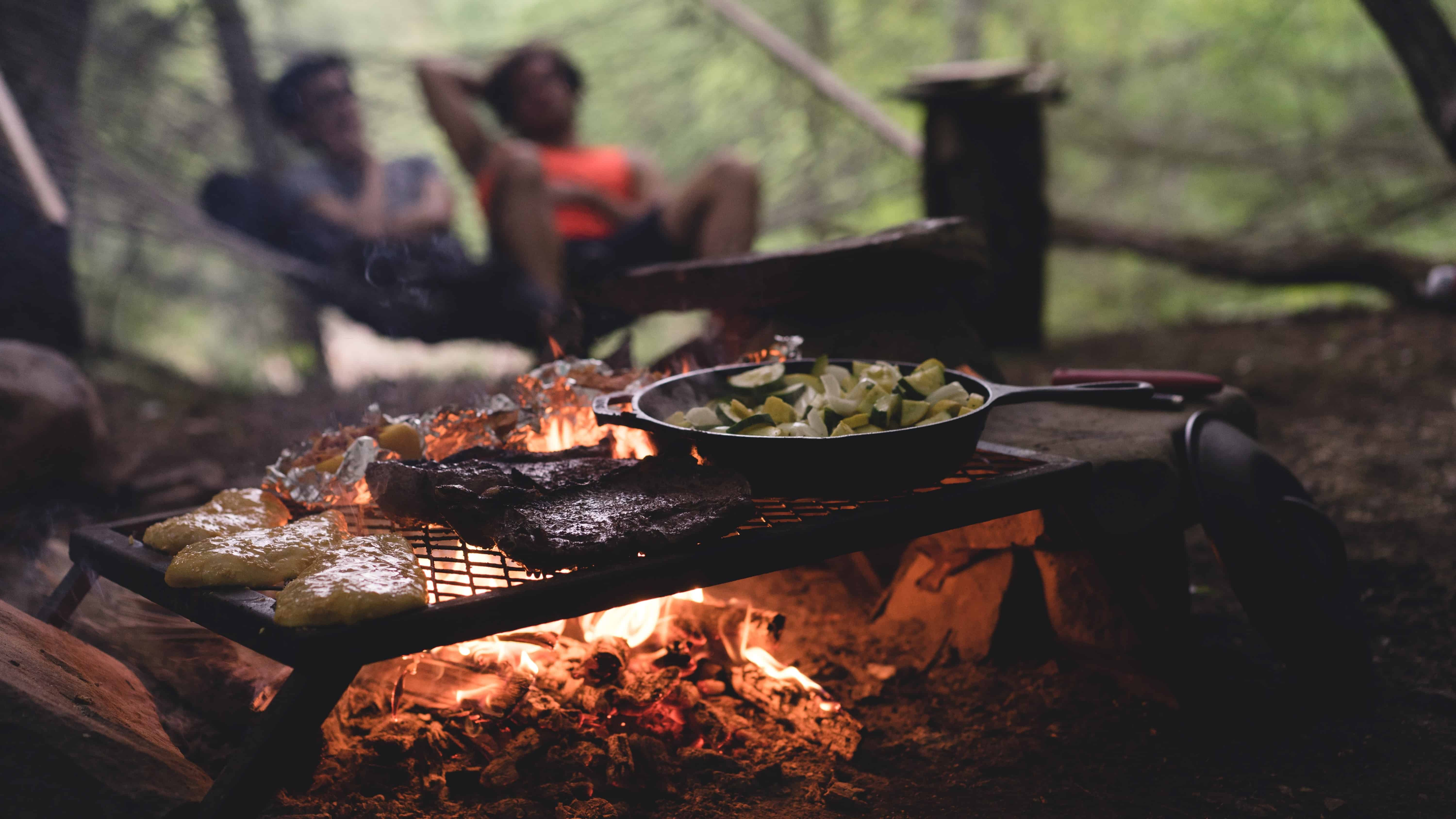 small grill with pans and foods over a campfire with blurry people sat in the distance