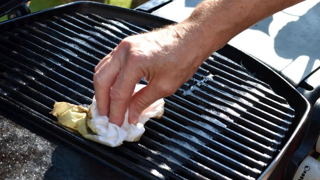 hand holding a cloth cleaning a bbq grill