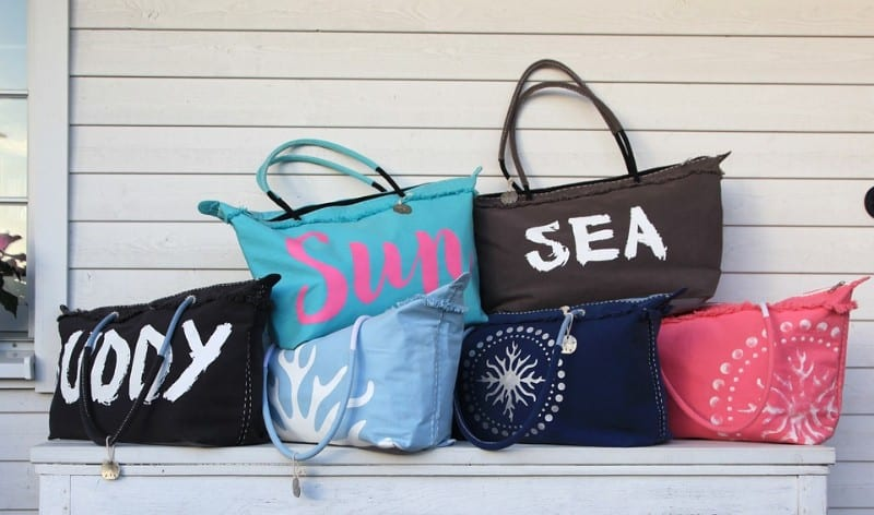 Beach bags with 'sea', 'sea' written on them against white clapperboard shed