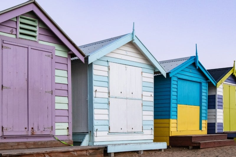brightly-coloured beach huts against a blue sky