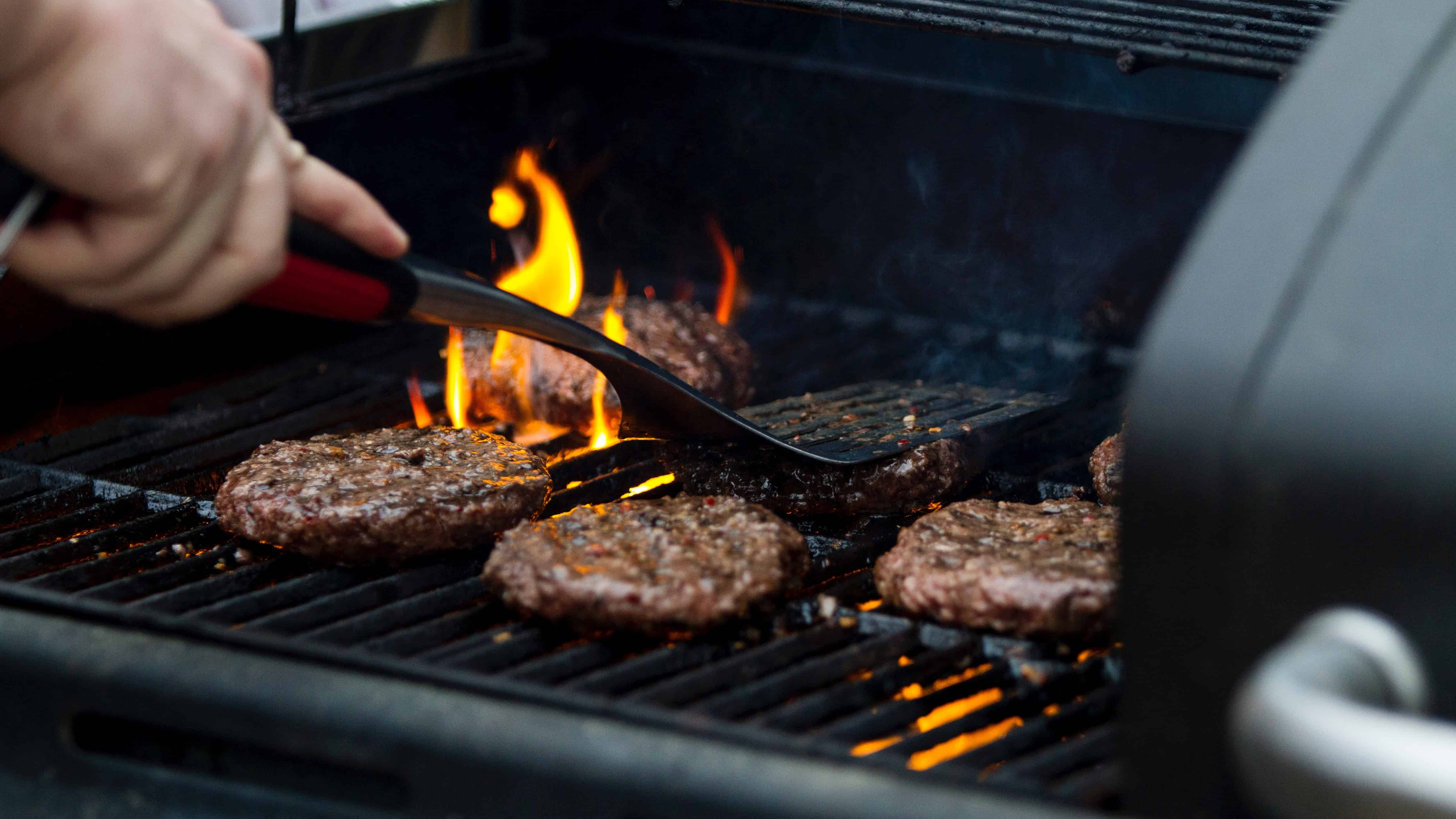 hand holding a BBQ utensil moving burger patties on a BBQ grill with fire coming off it