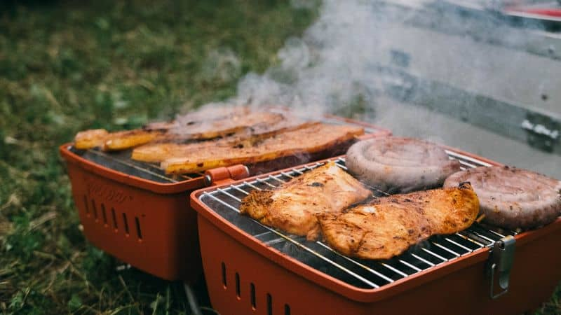 folded open BBQ grill cooking Cumberland whirl sausages and fish