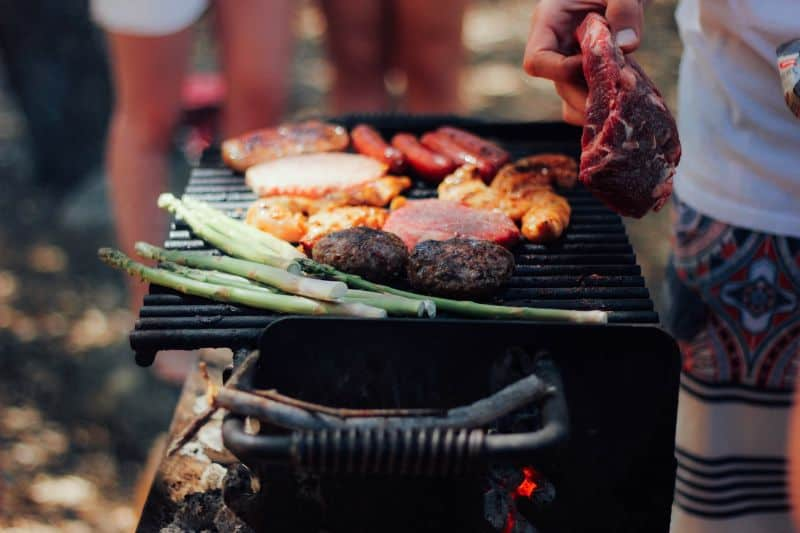 person tending a charcoal grill with sausages, bacon, burgers, and asparagus