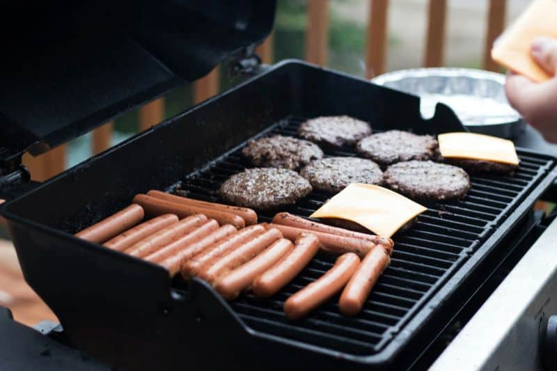 hand placing sliced cheese on burgers on a BBQ grill cooking sausages