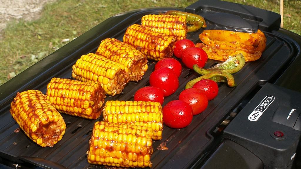 Corn and tomatoes grilling on an electric BBQ